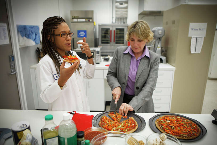 NASA's Advanced Food Technology Project manager Michele Perchonok, right, and Lockeed Martin Sr. Research Scientist Maya Cooper, try a pizza recipe being tested in a kitchen at Johnson Space Center Tuesday, July 3, 2012 in Houston, Texas. NASA is currently planning a mission to Mars, which has gravity, so more options for food preparation, like chopping vegetables, are available as opposed to the dehydrated fare of current space missions. (AP Photo/Michael Stravato) / FR29619 AP