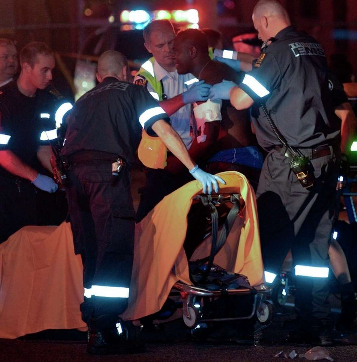 A man is attended to on the scene and loaded onto a gurney for transport following a shooting that left a least 19 injured and two dead in Toronto late Monday, July 16, 2012. The shooting took place after an altercation at an outdoor barbecue. (AP Photo/ THE CANADIAN PRESS/Toronto Star, Rick Madonik)
