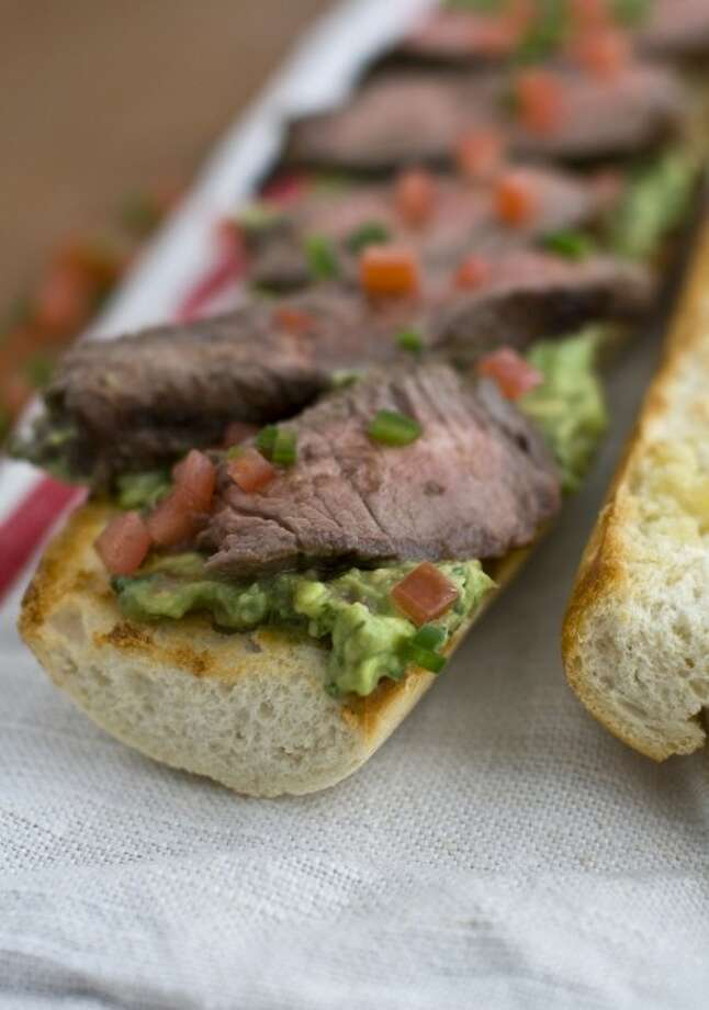 This March 21, 2011 photo shows vinaigrette-marinated sirloin with spicy guacamole in Concord, N.H. This recipe can be served as a generous entree or cut into thin strips across the grain and served on toasted baguette rounds and topped with the guacamole for a party. (AP Photo/Matthew Mead)
