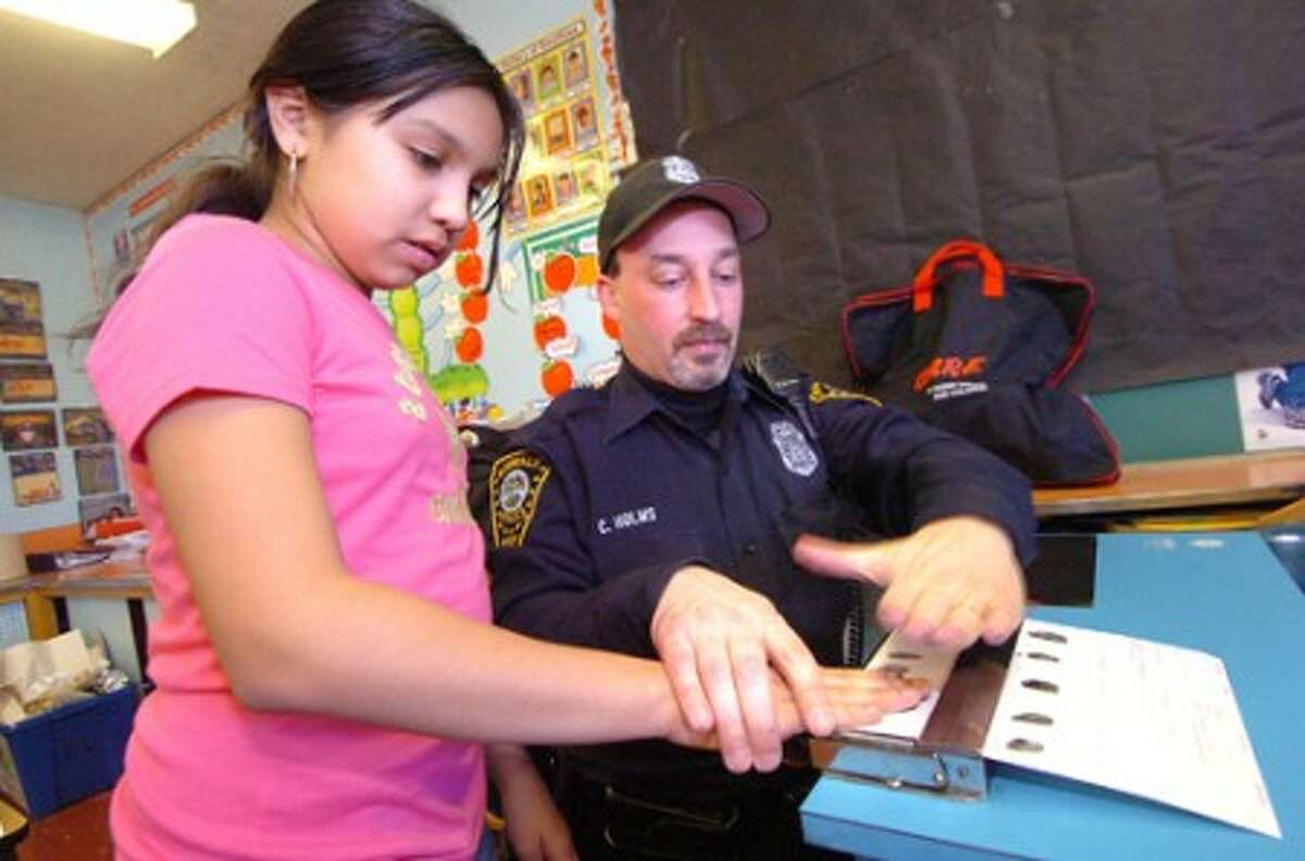 Photo/Alex von Kleydorff. Fox Run School 5th Grader, Kendra Valasquez gets fingerprinted by Norwalk Police Officer Chris Holms to see what its like during the ''Back to your Future'' pilot program in the Family Resource centers positive youth program.