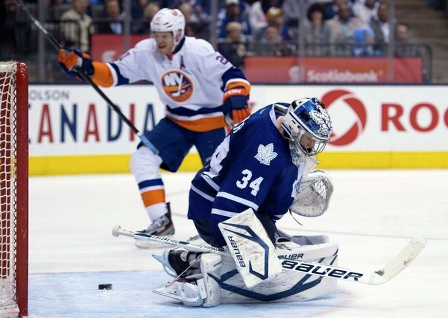 Toronto Maple Leafs goaltender James Reimer (34) reacts as New York Islanders Kyle Okposo, background, celebrates his team's fifth goal of an NHL hockey game during the third period in Toronto, Thursday, April 18, 2013. (AP photo/The Canadian Press, Frank Gunn) / The Canadian Press