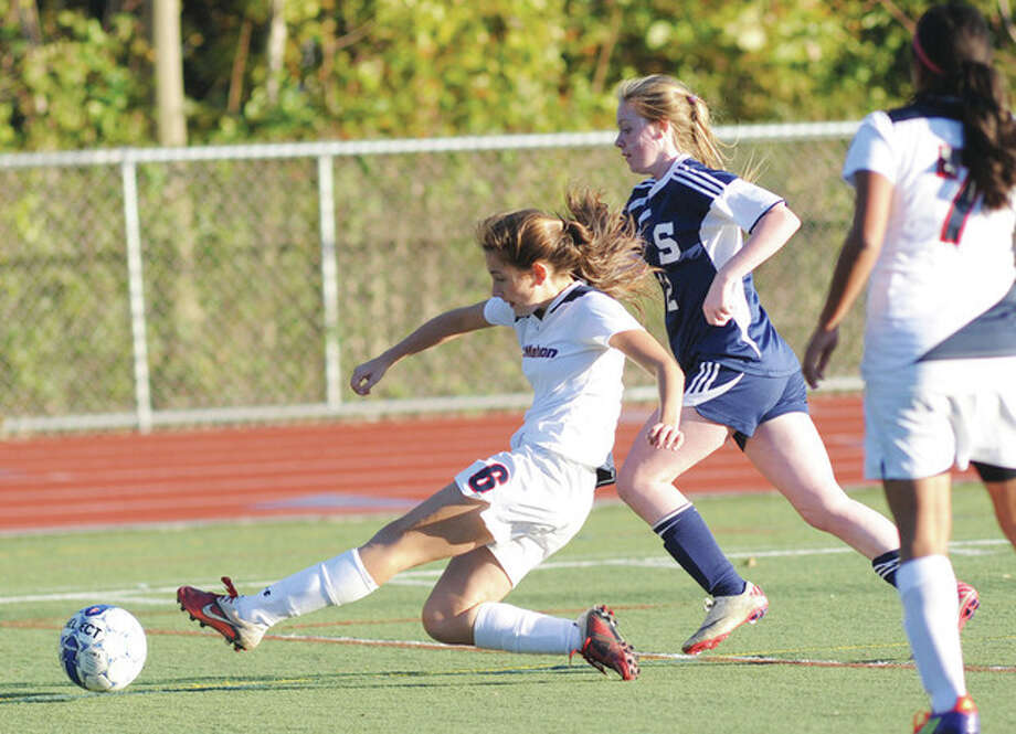 Hour photo/John Nash Brien McMahon's Maya Carter, left, slide tackles a ball away from Staples' Margaret Walsh as teammate Jasmin Hernandez, right, looks on during Tuesday afternoon's contest. The visiting Wreckers left McMahon with a 4-1 victory.
