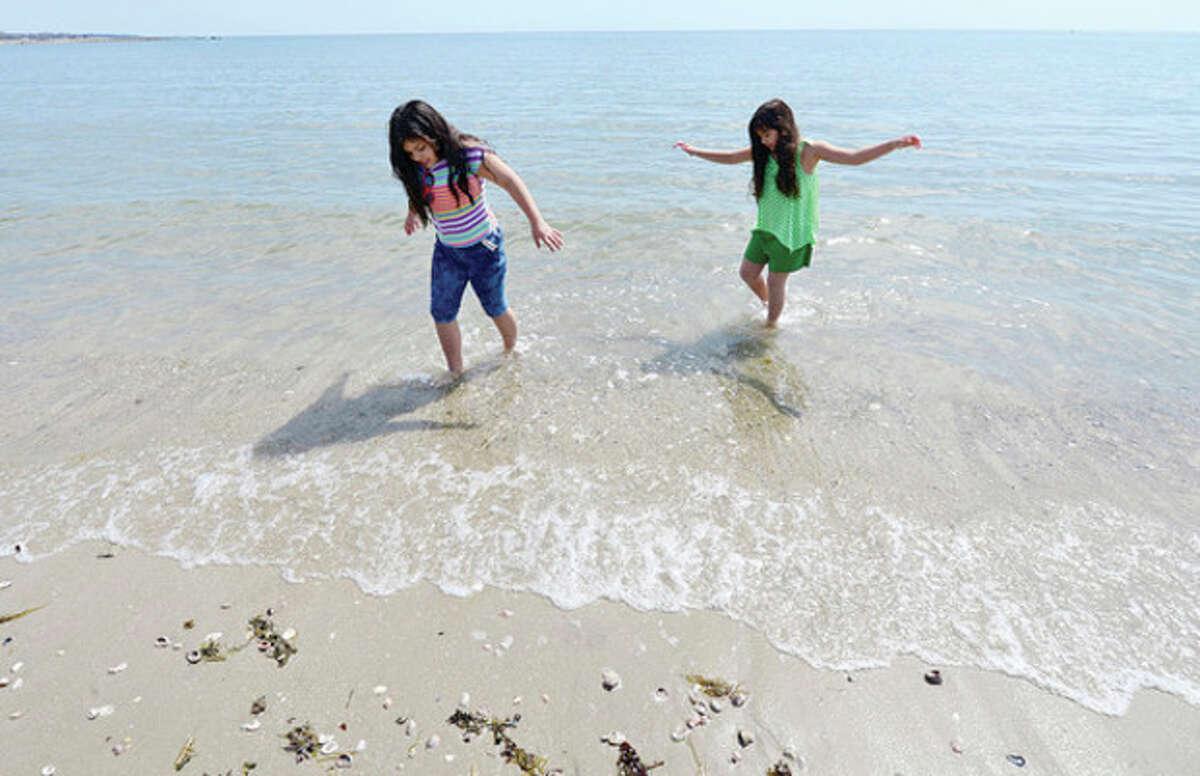Alyanna and Valentina Zavala, 10 and 8, test the water temperature at Compo Beach in Westport Tuesday. Hour photo / Erik Trautmann