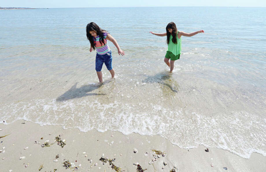 Alyanna and Valentina Zavala, 10 and 8, test the water temperature at Compo Beach in Westport Tuesday.Hour photo / Erik Trautmann / AP