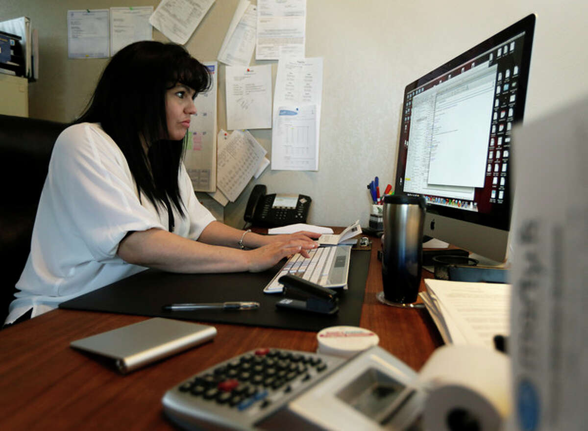 """In this Monday, April 15, 2013, photo, Consuelo Gomez, of the facilities management company """"Marty K"""" works in her office, Monday, April 15, 2013, in Bellevue, Wash. (AP Photo/Ted S. Warren)"""