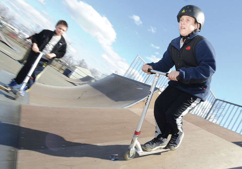 Jake Laycheck 13, takes turns with his friend Kali Dimitrov 9 Sunday on a sunny morning at the Calf Pasture Beach skate park. hour photo/Matthew Vinci
