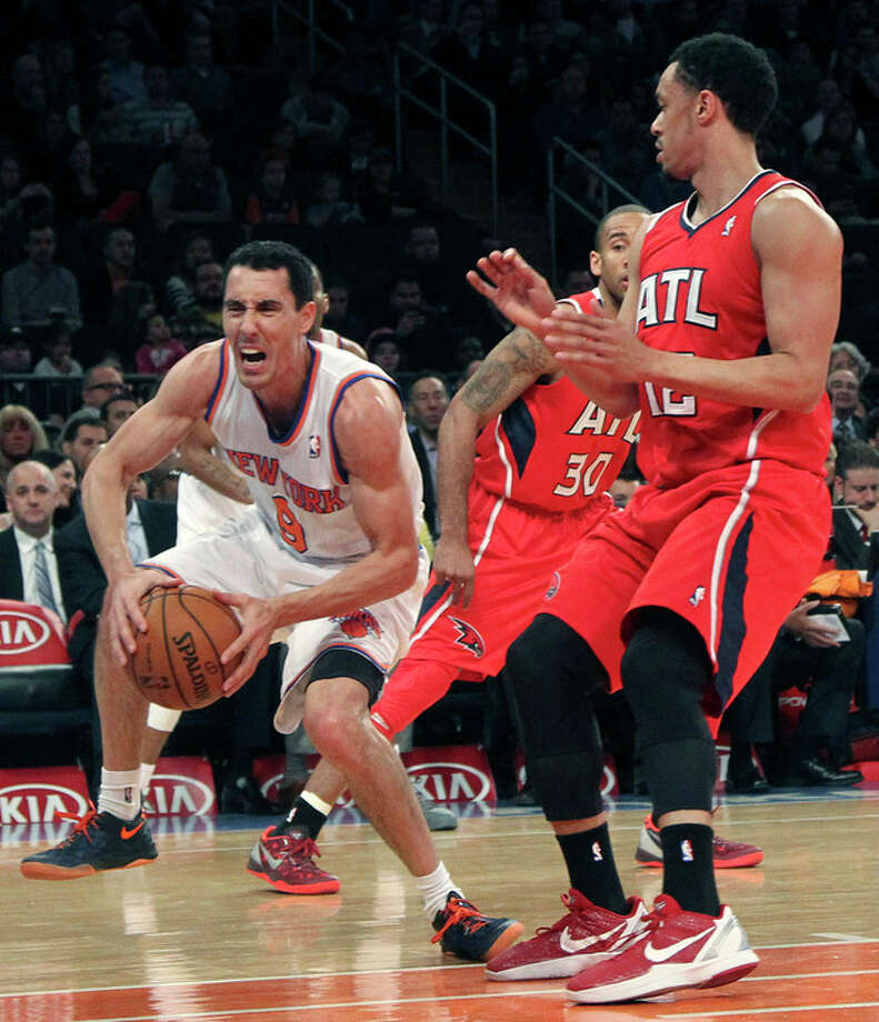 New York Knicks' Pablo Prigioni (9) grimaces as he injures his foot driving past Dahntay Jones (30) and Atlanta Hawks' John Jenkins during the first half of an NBA basketball game, Wednesday, April 17, 2013, at Madison Square Garden in New York. (AP Photo/Mary Altaffer) / AP