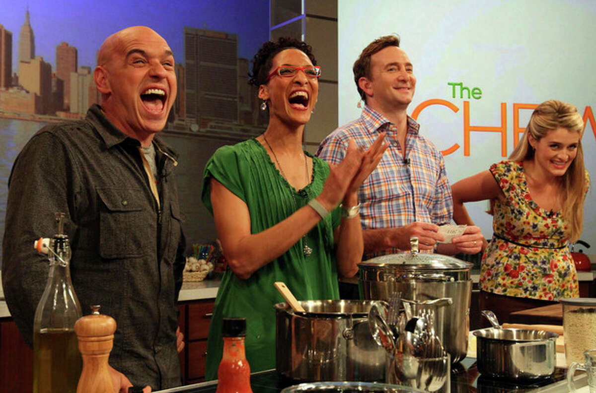 """AP photo / Tina Fineberg Co-hosts of ABC's """"The Chew"""", from left, Iron Chef Michael Symon, Carla Hall, Clinton Kelly and Daphne Oz react to audience applause during a rehearsal of the show in New York."""