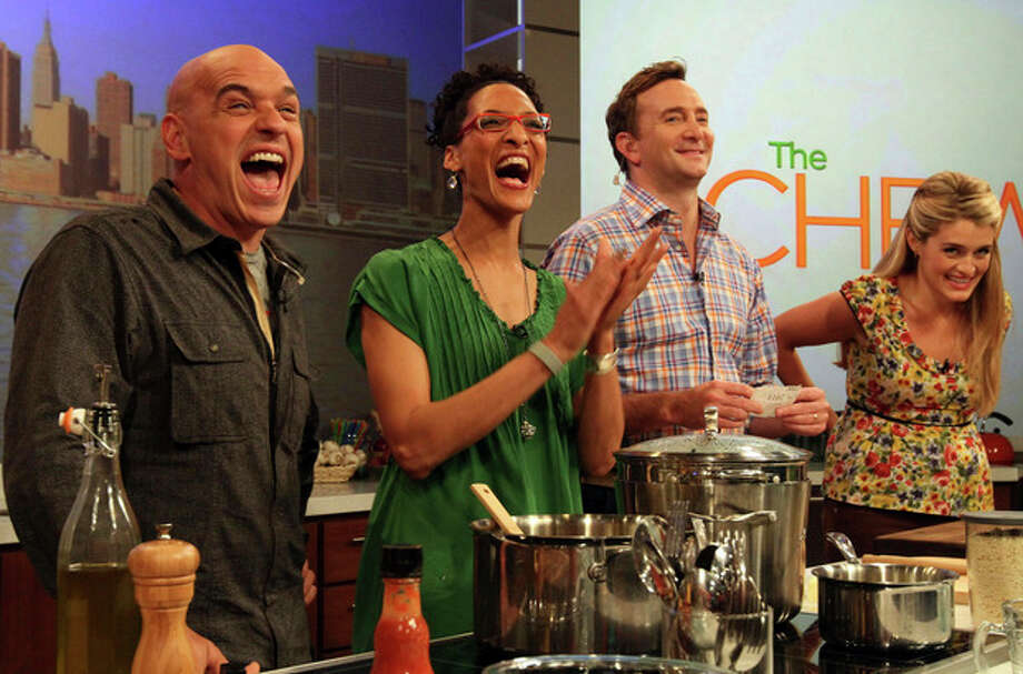 "AP photo / Tina Fineberg Co-hosts of ABC's ""The Chew"", from left, Iron Chef Michael Symon, Carla Hall, Clinton Kelly and Daphne Oz react to audience applause during a rehearsal of the show in New York. / FR73987 AP"