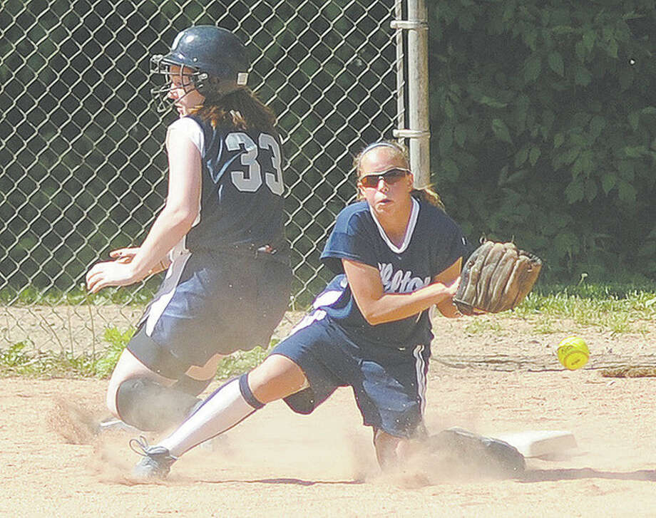Hour Photo/John Nash - Wilton third baseman Amy Salvato, right, can't come up with the throw from the outfielder as Staples Shannon Connors slide safe into the base during the fourth inning of Friday's game.