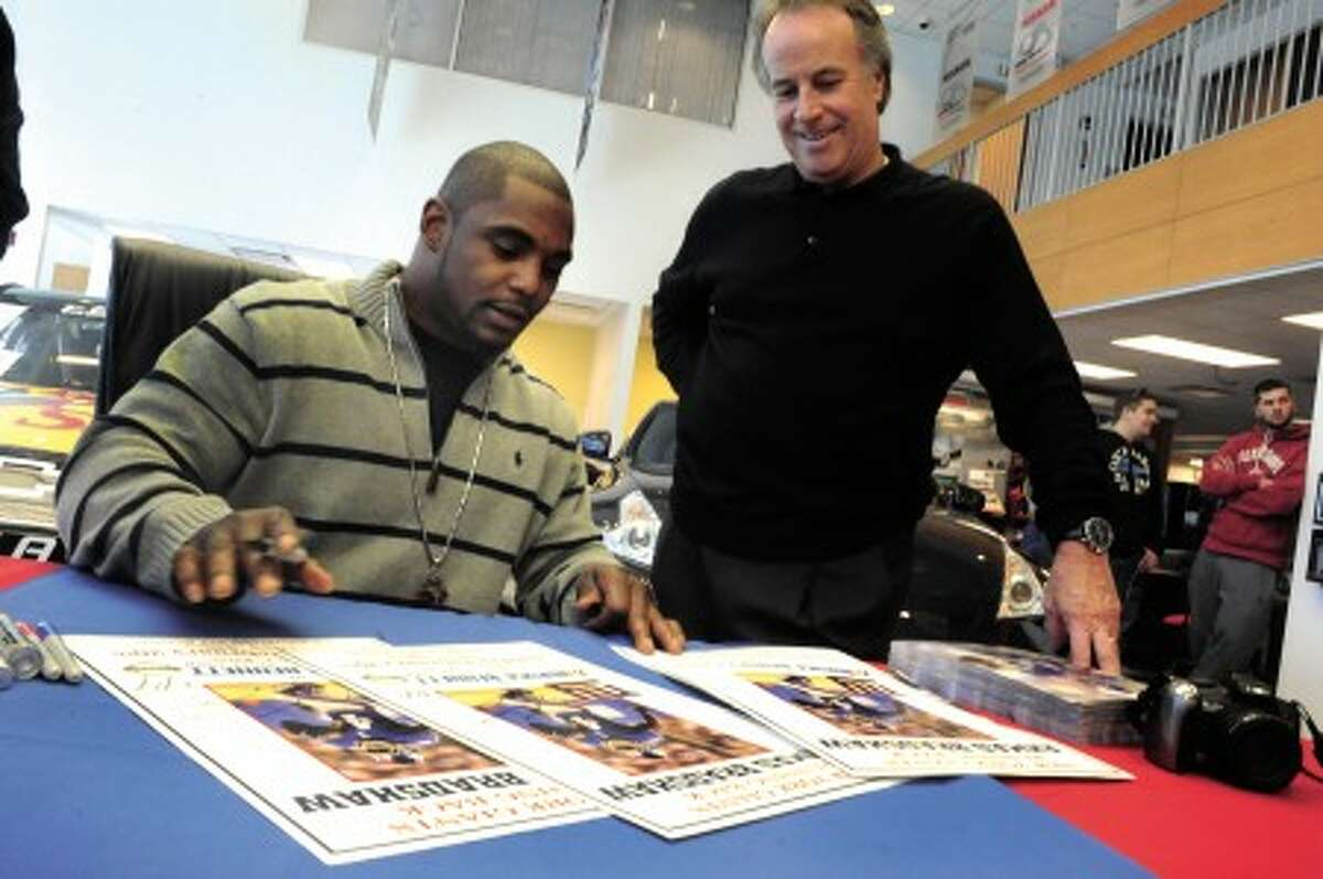 Ahmad Bradshaw, running back with the New York Giants with Bruce Bennett signs autographs at Bruce Bennett Nissan in Wilton on Sunday. photo/matthew vinci