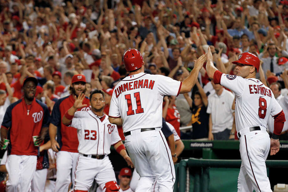 Washington Nationals' Ryan Zimmerman (11) celebrates with Danny Espinosa (8) after Zimmerman scored the winning run on a wild pitch from New York Mets relief pitcher Pedro Beato during the 10th inning of a baseball game Tuesday, July 17, 2012, in Washington. The Nationals won 5-4. (AP Photo/Alex Brandon) / AP