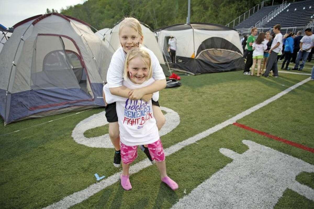Naomi Smith, 9, gets a piggy back ride from her sister Julia, 6, during Relay for Life on the Wilton High School Track Field Friday evening. Hour Photo / Danielle Robinson