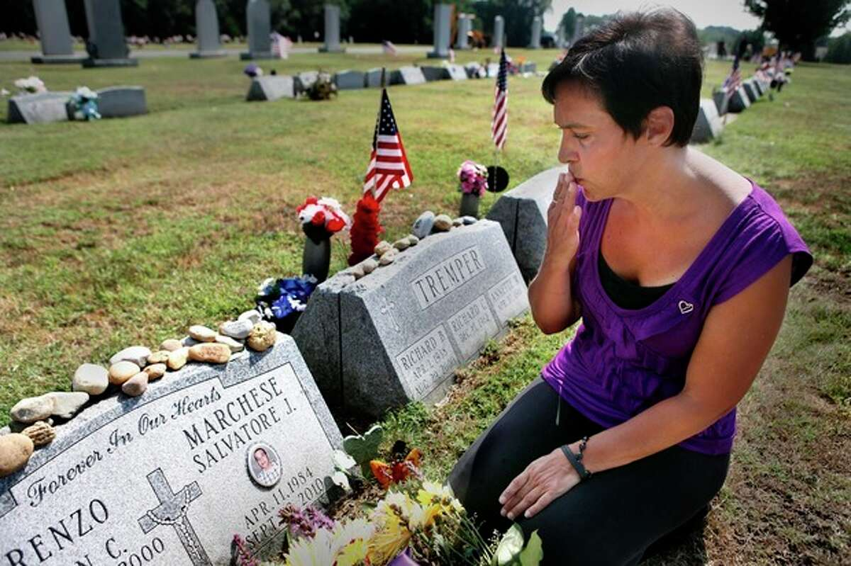 Patty DiRenzo puts her hand to her face to give a kiss to her son, Salvatore Marchese's grave, Monday, July 16, 2012, in Blackwood, NJ. DiRenzo's son died of a drug overdose on Sept. 23, 2010 and she is now a part of a nationwide push to make sure people won?'t be afraid of being arrested on drug possession charges to call 911 when someone has overdosed. (AP Photo/Brynn Anderson)