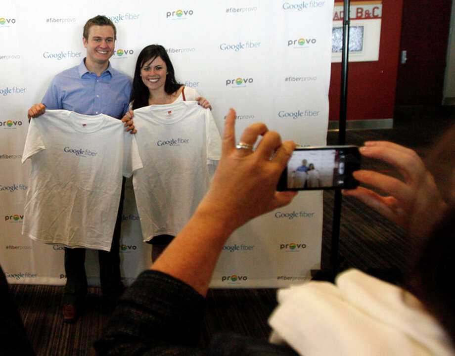 Steven Staples and Whitney Wing pose for photos with their Google Provo shirts after it was announced that Google will make Provo, Utah, the third city to get its high-speed Internet service via fiber-optic cables, Wednesday, April 17, 2013 in Provo. The Provo deal is the first time Google plans to acquire an existing fiber-optic system. The city of 115,000 created the fiber-optic network, iProvo, in 2004, which has struggled to break even. (AP Photo/The Salt Lake Tribune, Rick Egan) DESERET NEWS OUT; LOCAL TV OUT; MAGS OUT / The Salt Lake Tribune