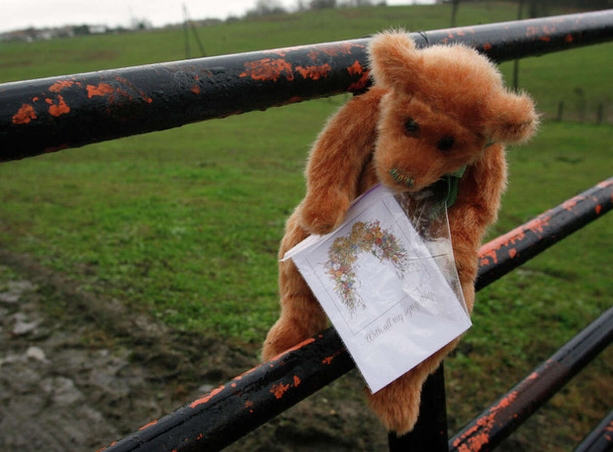 A stuffed animal with a sympathy card attached hangs from the locked gate at the Muskingum County Animal Farm Thursday, Oct. 20, 2011, in Zanesville, Ohio. The owner of a U.S. exotic animal farm who released dozens of tigers, lions and others beasts from their cages in a final act shot himself to death and then was bitten by one of his own animals, a sheriff said Thursday. An autopsy showed Terry Thompson had a bite wound on his head that appeared to have come from a large cat, such as a Bengal tiger, Muskingum County Sheriff Matt Lutz told a news conference. (AP Photo/Mike Munden)