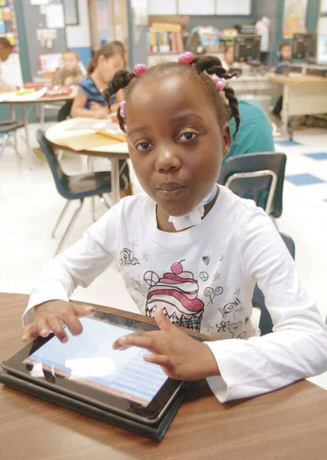 Hour photo / Erik Trautmann Due to a medical condition, Kendall Elementary School second-grader Amiya Bennett has lost most of her audible speech and uses and iPad with special software to allow her to communicate in class.