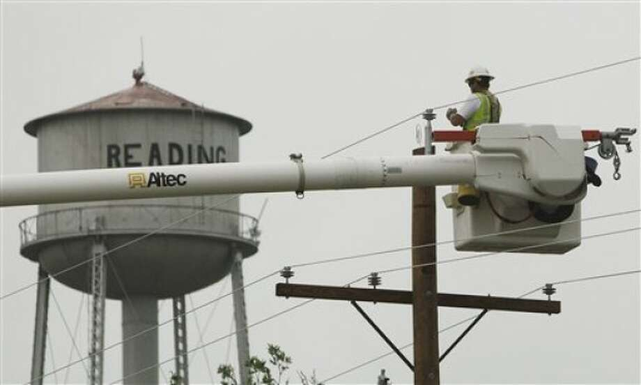 An unidentified power company worker helps restore power to Reading, Kan., Monday, May 23, 2011 after a weekend storm hit the small community Saturday night. The system brought tornadoes, hail, wind and rain to a corridor of northeast Kansas. About 200 homes were damaged in and around Reading, a town of about 250 residents. (AP Photo/Orlin Wagner)