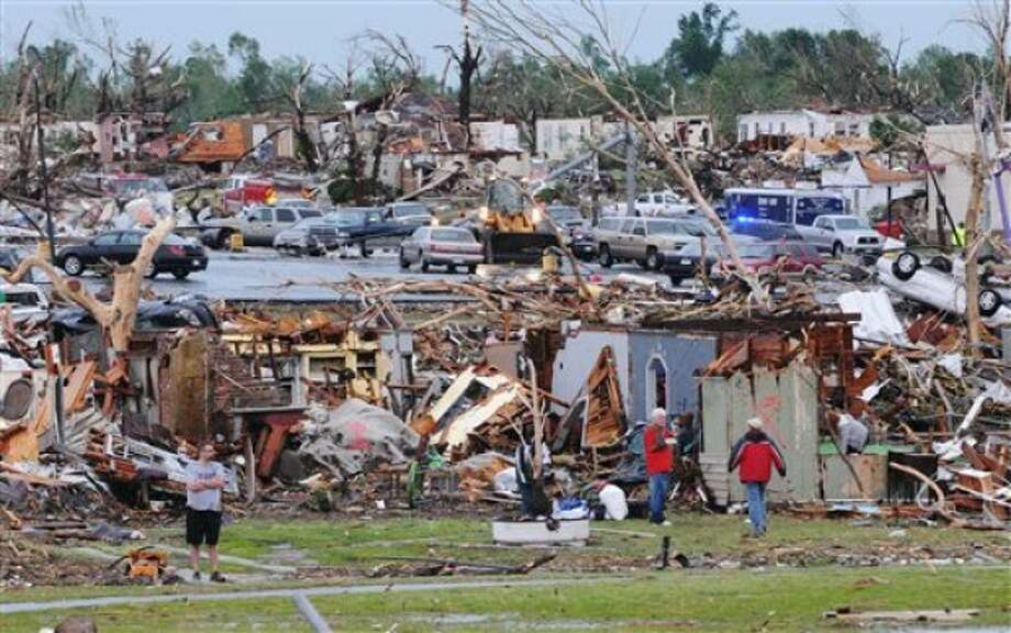 Residents of Joplin, Mo, survey the damage of their homes and city on Monday, May 23, 2011. A tornado that struck Joplin, Mo, on Sunday, May 22, killed at least 89 and injured hundreds more. (AP Photo/Mike Gullett)