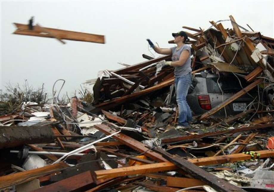 Sabrina Banspmer tosses a board from the destroyed home of her grandmother in Joplin, Mo, on Monday, May 23, 2011. Banspmer was doing what many Joplin residents were busy with on Monday, trying to salvage anything from their homes that were damaged or destroyed by the tornado that struck on Sunday. (AP Photo/Mike Gullett)