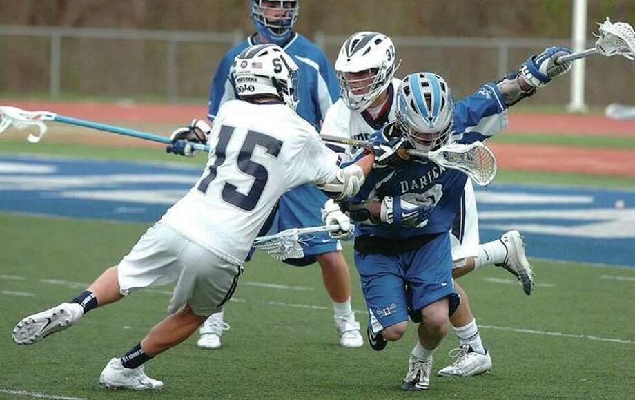 Hour photo/Alex von KleydorffStaples Will Johnson (15) engages in some close order combat against William Hammermick of Darien during Tuesday's game in Westport. The two squads battled tooth-and-nail before the visiting Blue Wave emerged with a 5-3 victory / 2013 The Hour Newspapers