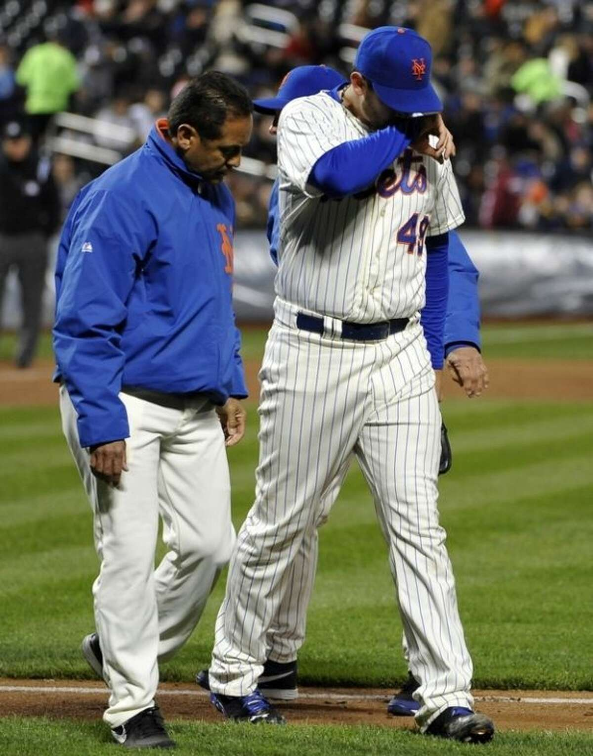 New York Mets trainer Ray Ramierez and manager Terry Collins, rear, help starting pitcher Jonathon Niese off the field after he was hit in the right foot by a ball hit by Los Angeles Dodgers' A.J. Ellis in the third inning of a baseball game at Citi Field, Tuesday, April 23, 2013, in New York. Niese left the game. (AP Photo/Kathy Kmonicek)