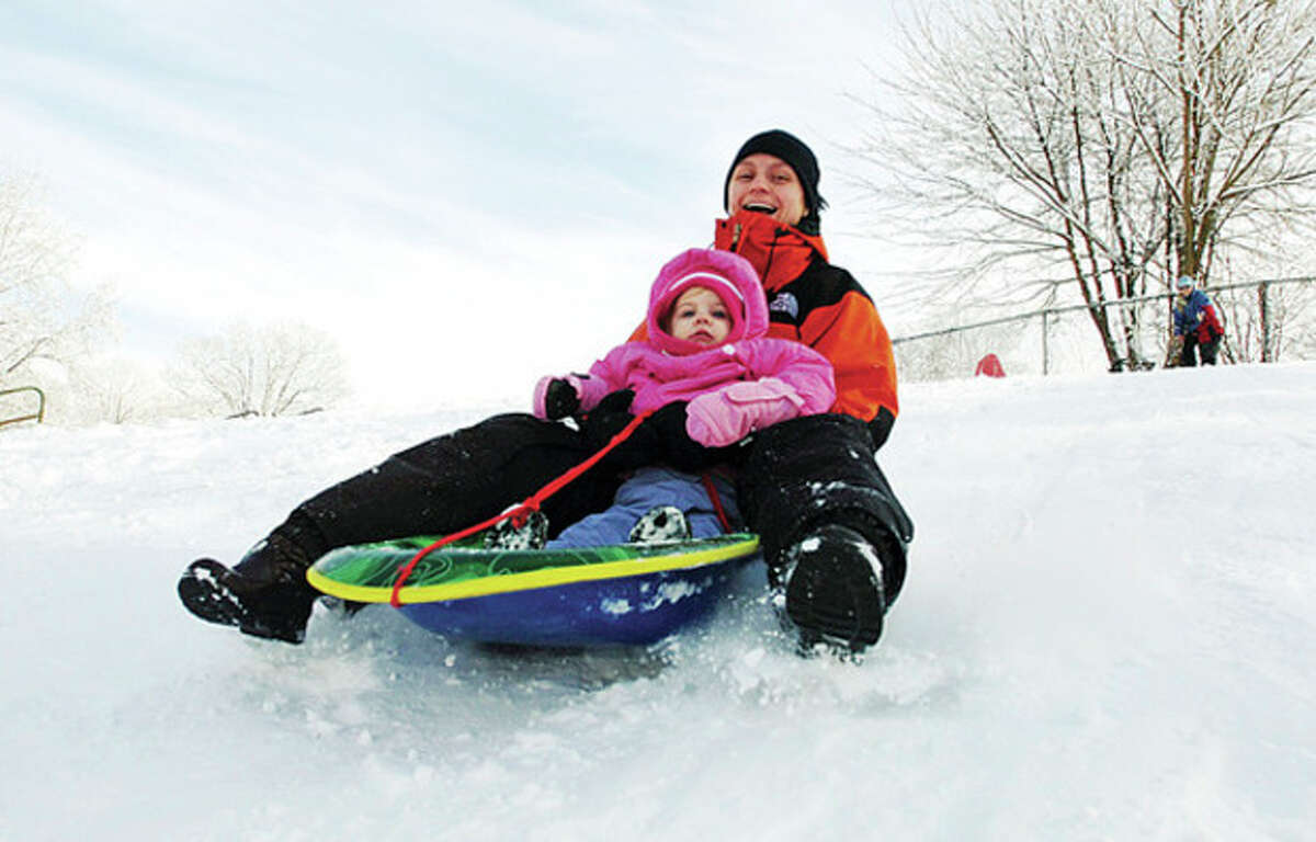 Megan Chrysler sleds at Wolfpit Elementary School in Norwalk with her daughter Evelyn, 20 months, on Saturday. Hour photo / Erik Trautmann