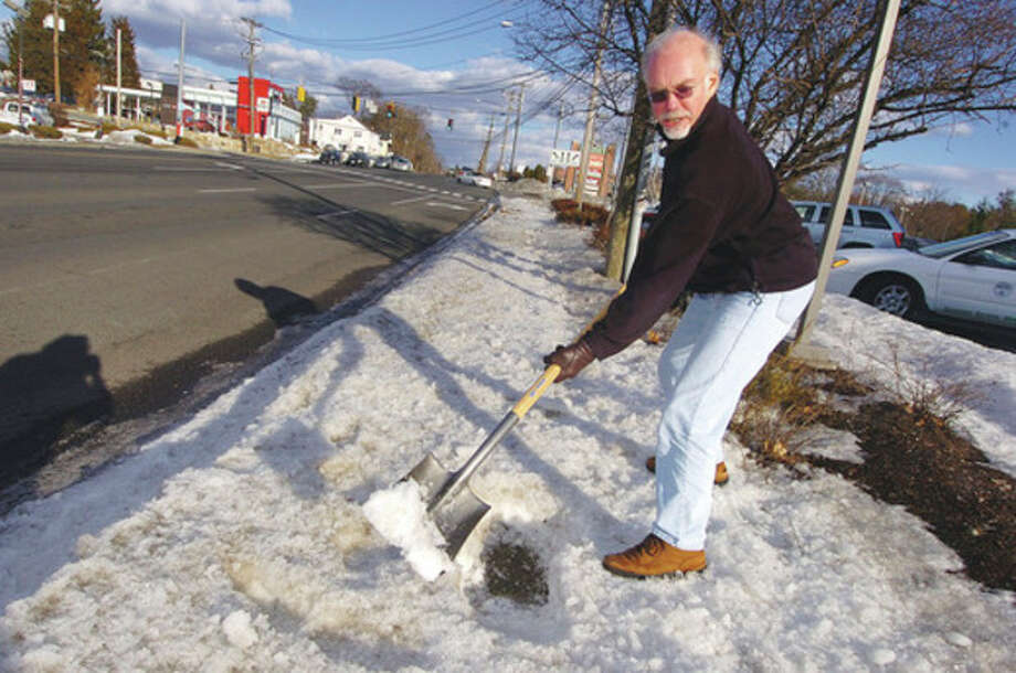 Photo/Alex von Kleydorff. Ordinance Enforcement Officer Larry Losio uses a shovel along Westport Ave to check if there is sidewalk or dirt underneath snow, business owners have to comply with the snow removal ordinance. / © 2010 The Hour Newspapers/Alex von Kleydorff
