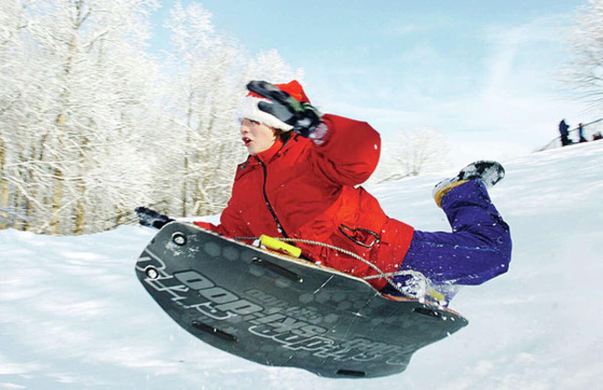 Alex Robichaud, 13, takes to the air while sledding at Wolfpit Elementary School in Norwalk on Saturday. Hour photo / Erik Trautmann