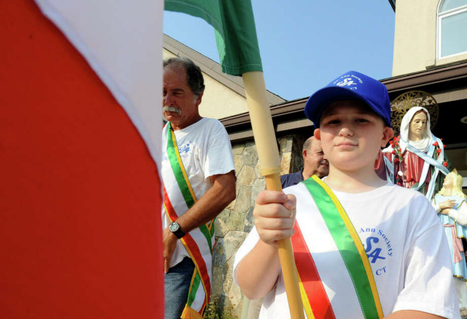 Dylan Ehlers 10, heads the St. Ann's Club feast procession on Thursday. hour photo/matthew vinci