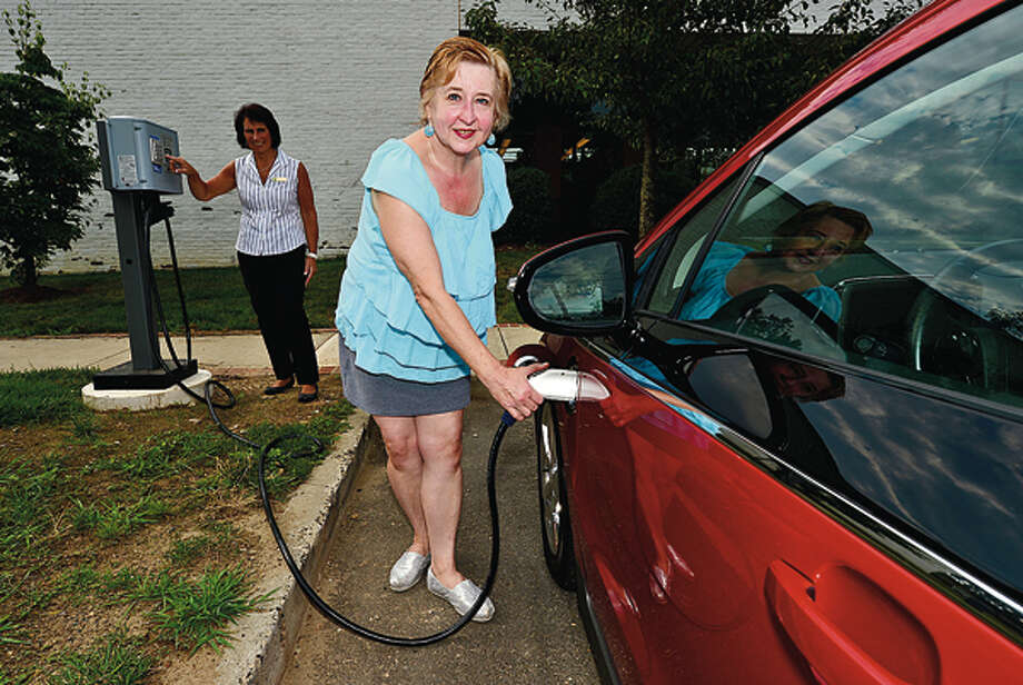 Wilton Public Library patron, Eileen Ferro, charges her Chevy Volt at the new charging station as library head off building operations Joan Waldie looiks on Wednesday. Hour photo / Erik Trautmann / ©2012 The Hour Newspapers