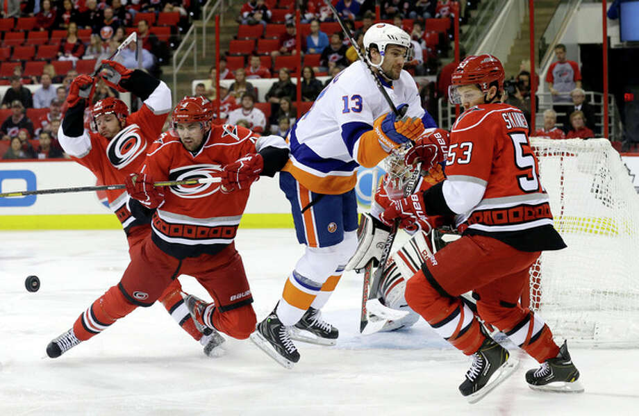 New York Islanders' Colin McDonald (13) tries to take a shot against Carolina Hurricanes goalie Dan Ellis, rear, as Jeff Skinner (53), Jamie McBain (4) and Marc-Andre Bergeron, left, defend during the first period of an NHL hockey game in Raleigh, N.C., Tuesday, April 23, 2013. (AP Photo/Gerry Broome) / AP