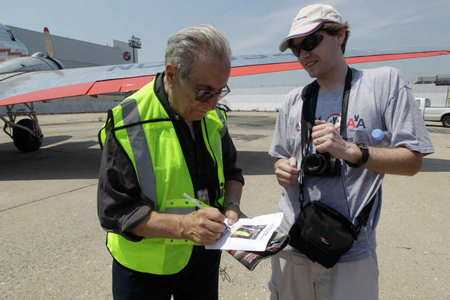 "Azriel ""Al"" Blackman signs an autograph for an aviation enthusiast after flying in a DC-3, Wednesday, July 18, 2012 in New York. American Airlines is celebrating the 70-year service of a New York City mechanic who says he has no plans to retire. Azriel ""Al"" Blackman was 16 years old when he started as an apprentice mechanic in July of 1942. (AP Photo/Mary Altaffer) / AP"