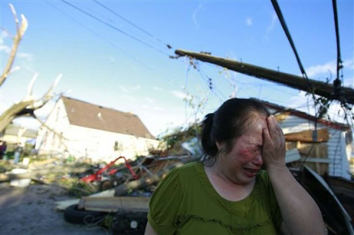 Chue Vang, 50, reacts after coming home to discover that her home was damaged after a tornado struck northern Minneapolis Sunday, May 22, 2011. At least one person was killed and at least 29 were injured in the storm. (AP Photo/The Star Tribune, Jerry Holt) MANDATORY CREDIT; ST. PAUL PIONEER PRESS OUT; MAGS OUT; TWIN CITIES TV OUT