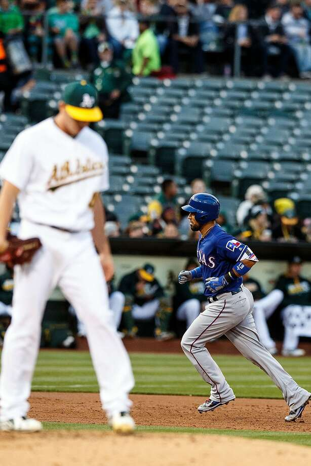 OAKLAND, CA - JUNE 14:  Robinson Chirinos #61 of the Texas Rangers rounds the bases after hitting a three run home run off of Eric Surkamp #48 of the Oakland Athletics during the second inning at the Oakland Coliseum on June 14, 2016 in Oakland, California. (Photo by Jason O. Watson/Getty Images) Photo: Jason O. Watson, Getty Images