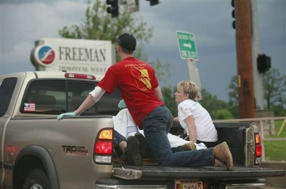 A pickup truck with what looked like two rescue workers and two injured people weaves in and out of traffic to get to Freeman Hospital West in Joplin, Mo. after the town was hit by a tornado on Sunday, May 22, 2011. (AP Photo/The Wichita Eagle, Jaime Green)