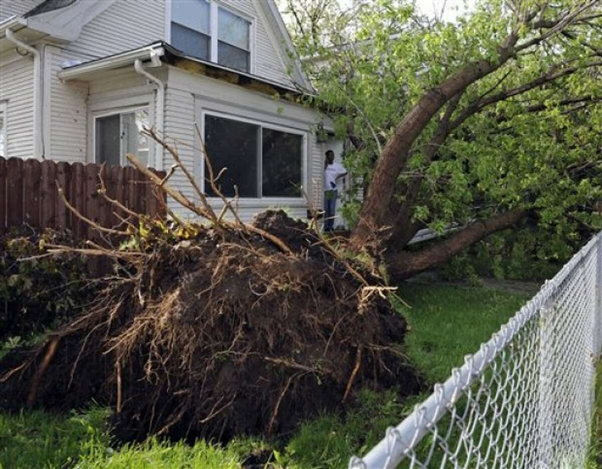 Essie McKenzie peers out the front door to survey the damage to her front yard after a tornado struck northern Minneapolis Sunday, May 22, 2011, causing extensive property damage, killing at least one person and injuring at least 18 others. (AP Photo/Craig Lassig)