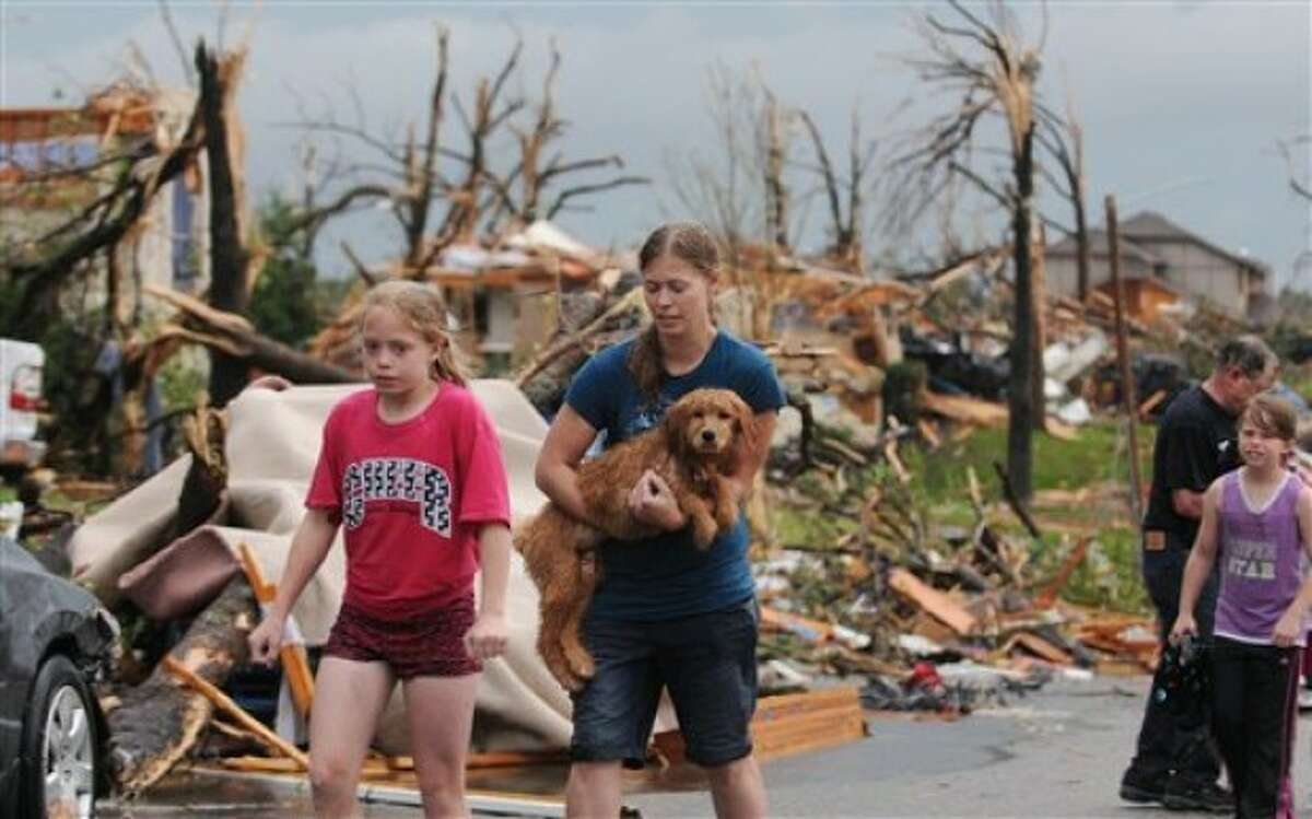 On this Sunday, May 22, 2011 photo, two young Joplin, Mo, residents carry their dog and head to a rescue center after their home was destroyed by a tornado that hit the southwest Missouri city on Sunday evening. The tornado tore a path a mile wide and four miles long destroying homes and businesses.(AP Photo/Mike Gullett)