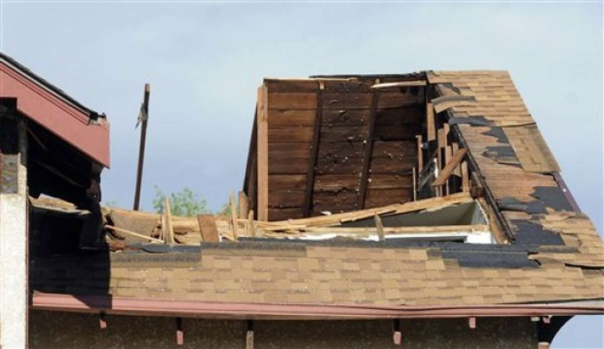 Damage to a roof is shown after a tornado struck northern Minneapolis Sunday, May 22, 2011, causing extensive property damage, killing at least one person and injuring at least 18 others. (AP Photo/Craig Lassig)