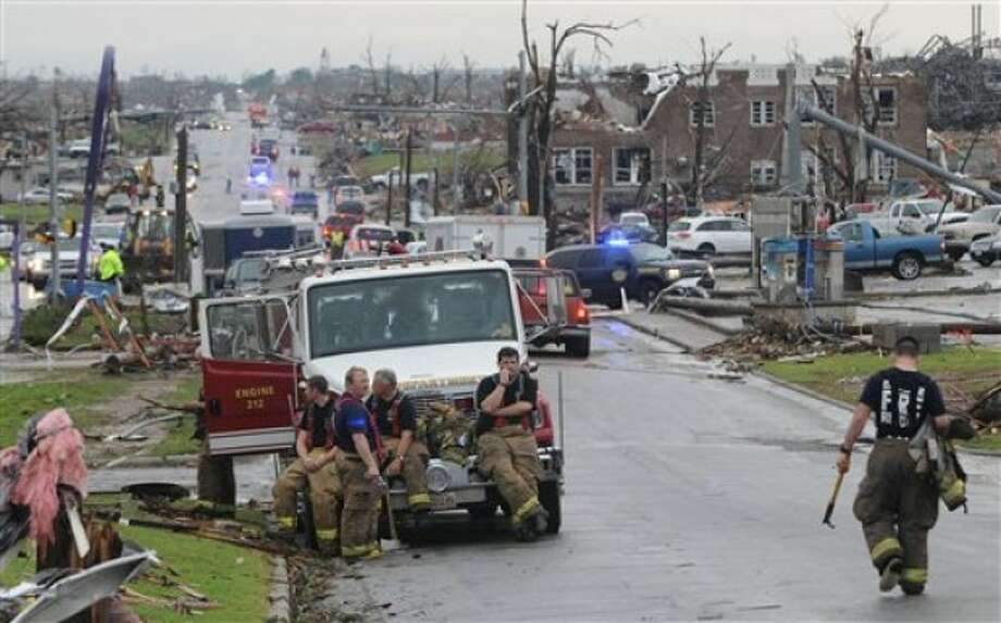 Nevada Missouri firefighters take a break from search and rescue work in Joplin, Mo, on Monday, May 23, 2011. Fire and rescue workers from neighboring cities and states have joined the rescue effort from the tornado that struck Joplin on Sunday, May 22. (AP Photo/Mike Gullett)