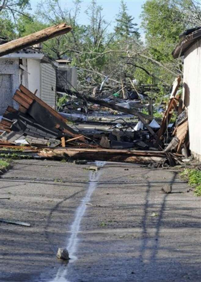 Power lines and debris clog an alley after a tornado struck northern Minneapolis, Sunday, May 22, 2011, causing extensive property damage, killing at least one person and injuring at least 18 others. (AP Photo/Craig Lassig)