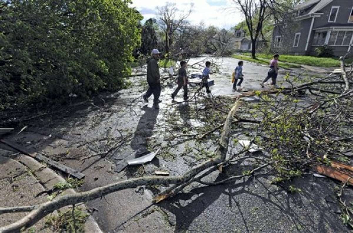 Local residents work their way down a street and around trees after a tornado struck northern Minneapolis, Sunday, May 22, 2011, causing extensive property damage, killing at least one person and injuring at least 18 others. (AP Photo/Craig Lassig)