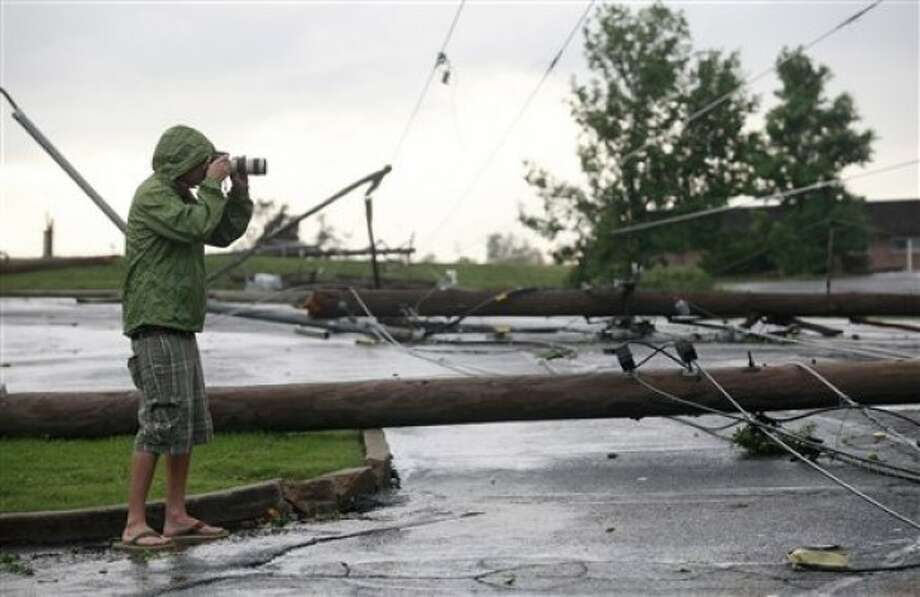 A photographer shoots some of the damage near St. Joseph Hospital in Joplin, Mo., after the town was hit by a tornado on Sunday, May 22, 2011. (AP Photo/The Wichita Eagle, Jaime Green)