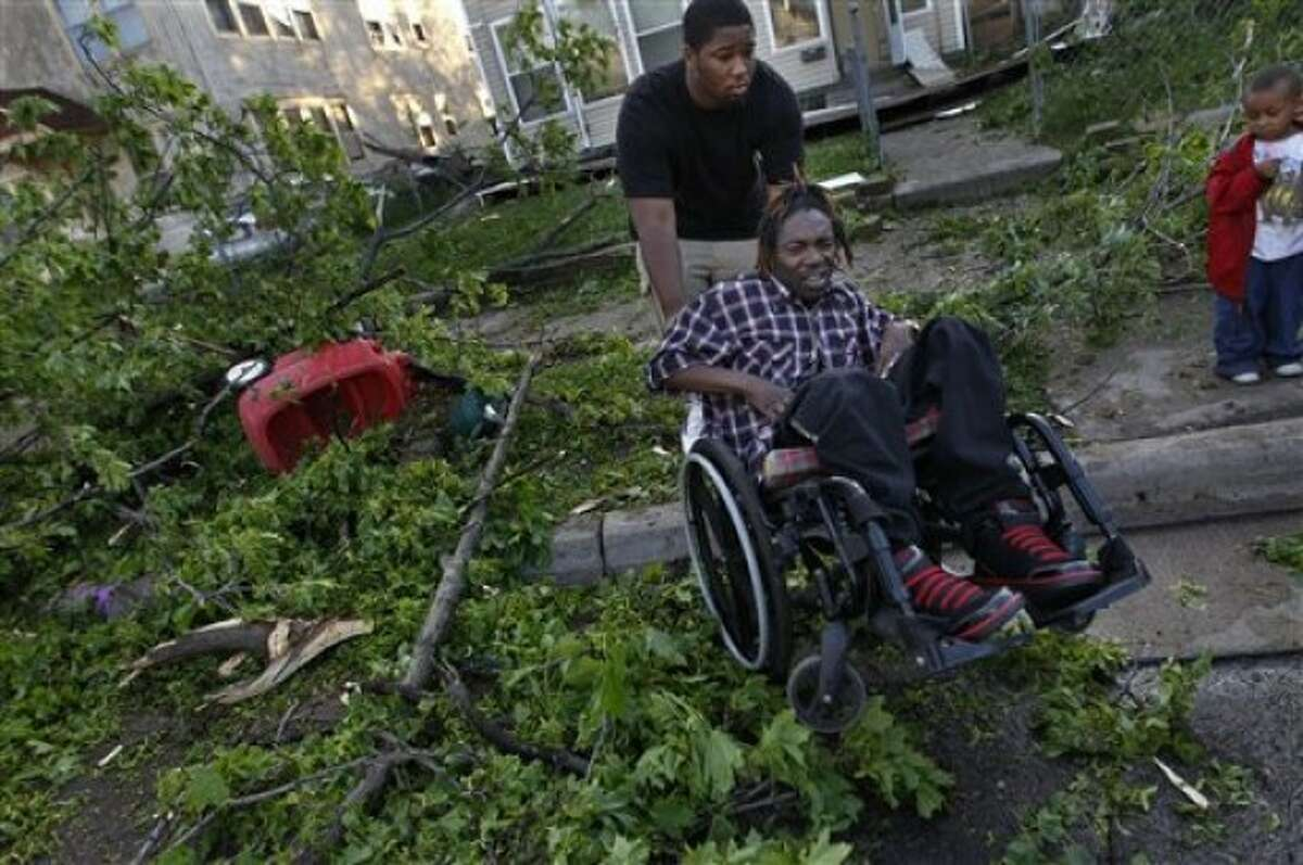 Dwayne Riley, in wheelchair, is helped down from the curb by his son Andrew Hubbard in north Minneapolis, Sunday, May 22, 2011. His son also helped him into the basement when the storm hit. (AP Photo/The Star Tribune, Richard Tsong-Taatarii)