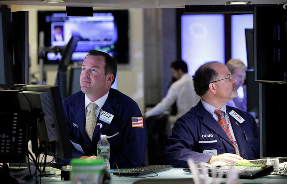 FILE- In this Tuesday, July 17, 2012, file photo, Specialists Charles Boeddinghaus, left, and Douglas Johnson, work at their posts on the floor of the New York Stock Exchange Tuesday, July 17, 2012. Renewed hope for more help from the Fed supported markets, as did positive earnings statements from Goldman Sachs, Coca Cola and Yahoo. U.S. earnings statements will remain a focus of attention later. (AP Photo/Richard Drew, File) / AP
