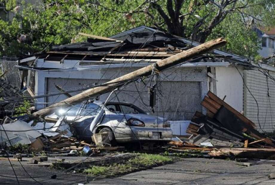 Power lines and debris clog an alley after a tornado struck northern Minneapolis Sunday, May 22, 2011, causing extensive property damage, killing at least one person and injuring at least 18 others. (AP Photo/Craig Lassig)
