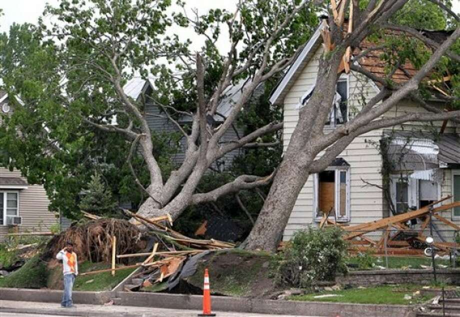 A man walks past trees that fell onto houses along West Ave. in La Crosse, Wis. on Monday May 23, 2011. Residents of La Crosse were cleaning up after a tornado blew through the city on Sunday, May 22, 2011. (AP Photo/The La Crosse Tribune, Erik Daily)