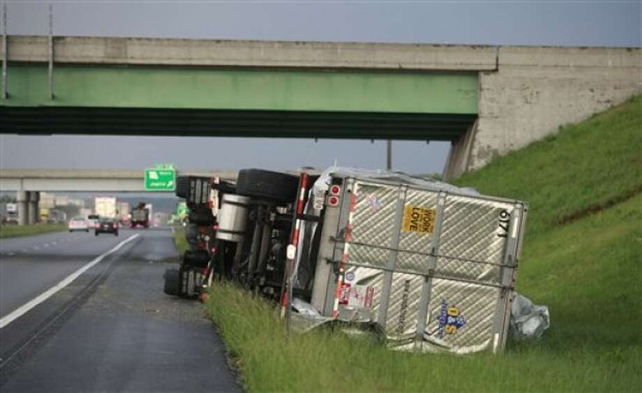 A tractor trailer is tipped over on Interstate 44 near Joplin, Mo., after the town was hit by a tornado on Sunday, May 22, 2011. (AP Photo/The Wichita Eagle, Jaime Green)