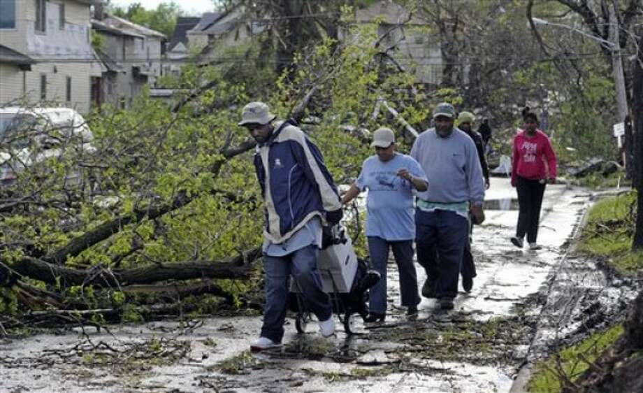 Local residents work their way around trees and downed power lines after a tornado struck northern Minneapolis, Sunday, May 22, 2011, causing extensive property damage, killing at least one person and injuring at least 18 others. (AP Photo/Craig Lassig)