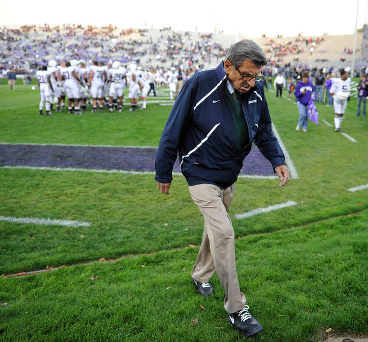 """FILE - In this Oct. 22, 2011 file photo, Penn State coach Joe Paterno walks off the field after warmups before an NCAA college football game against Northwestern in Evanston, Ill. NCAA president Mark Emmert says he isn't ruling out the possibility of shutting down the Penn State football program in the wake of the Jerry Sandusky child sex abuse scandal. In a PBS interview Monday night, July 16, 2012, he said he doesn't want to """"take anything off the table"""" if the NCAA determines penalties against Penn State are warranted. (AP Photo/Jim Prisching, File)"""